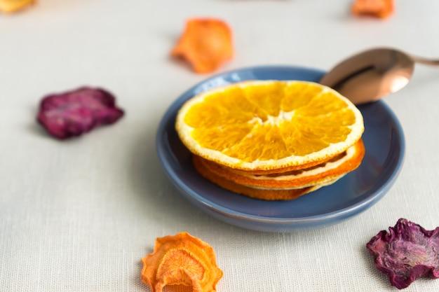 Gesundes essen bio-ernährung. geschnittener und getrockneter apfel, orange, karotte und rote-bete-wurzeln auf textilhintergrund.