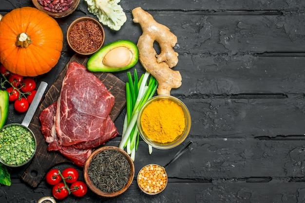 Gesundes essen. bio-sortiment mit rohen rindersteaks. auf einem schwarzen rustikalen hintergrund.