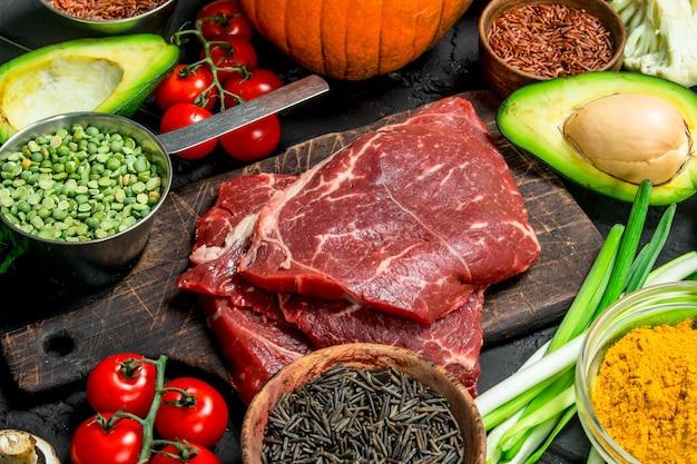 Gesundes essen. bio-sortiment mit rohen rindersteaks. auf einem schwarzen rustikalen.