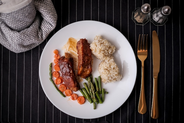 Gesundes essen. diät essen abendessen gericht. schweinerippchen und grüne bohnen, karotten, quinoa.