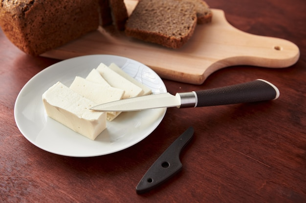 Gesundes essen - frisches brot und feta-käse auf einem hölzernen hintergrund