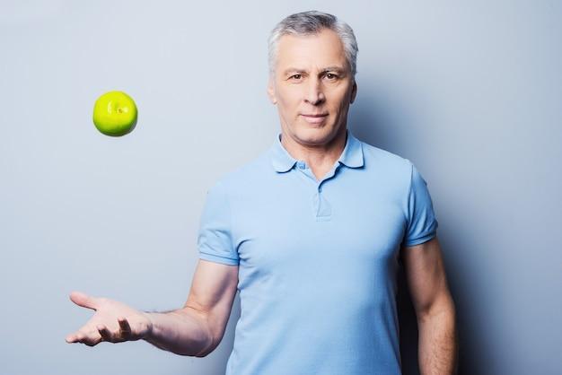 Gesundes essen für den erfolg. selbstbewusster älterer mann, der beiläufig einen grünen apfel hochwirft und lächelt, während er vor grauem hintergrund steht