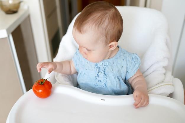Gesundes essen für kinder. entzückendes kleines baby, das in ihrem stuhl sitzt und mit gemüse spielt