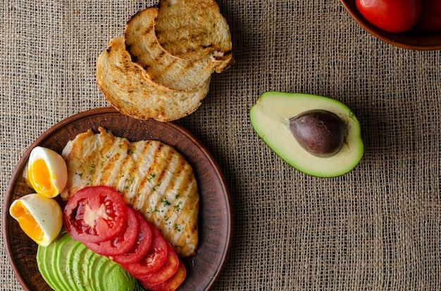 Gesundes essen gegrillte hähnchenbrust mit avocado, tomaten, toast und weichem gekochtem ei. flache lage, exemplar