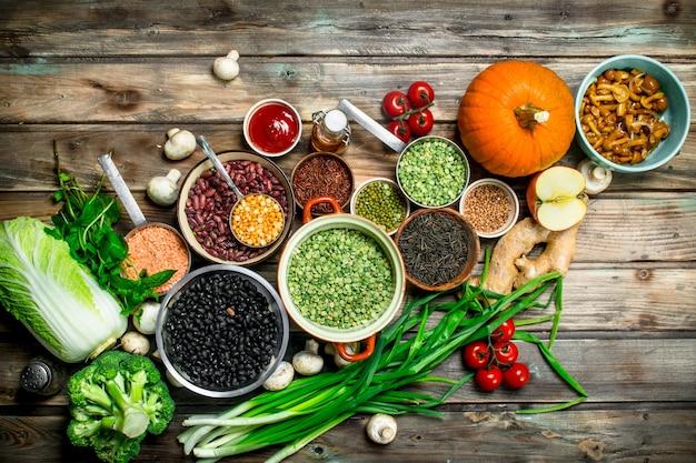 Gesundes essen. gesundes sortiment an obst und gemüse mit hülsenfrüchten. auf einem holz.