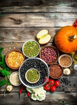 Gesundes essen. gesundes sortiment an obst und gemüse mit hülsenfrüchten. auf einer holzoberfläche.