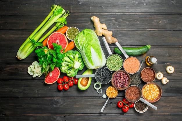 Gesundes essen. getreidesortiment mit hülsenfrüchten und bio-gemüse. auf einer holzoberfläche.