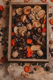 Gesundes essen getrocknete früchte. trockenpflaumen, getrocknete aprikosen, rosinen, feigen, nüsse. ansicht von oben. platz kopieren.