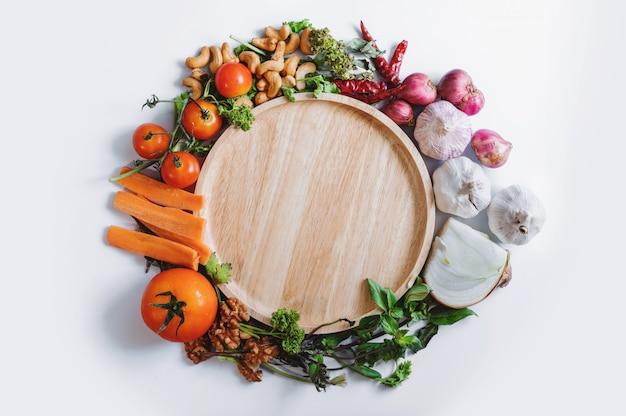 Gesundes essen. holzgericht umgeben mit gesundem frischem gemüse