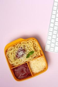 Gesundes essen in plastikbehältern essfertig mit hausgemachten spaghetti mit tomaten, käse und basilikum auf dem arbeitstisch. italienisches essen. wegnehmen.
