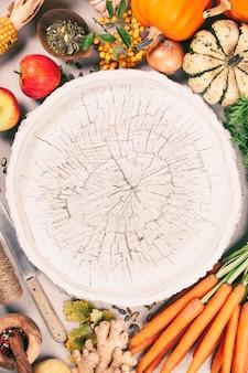 Gesundes essen kochen hintergrund. frische gartenkarotten, kürbise, zwiebeln, äpfel und gewürze auf rustikalem hintergrund