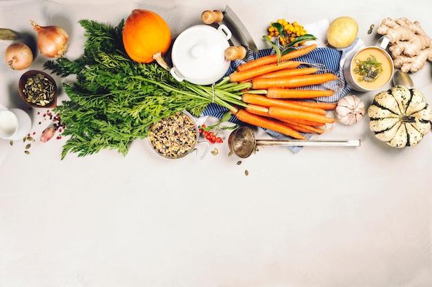 Gesundes essen kochen hintergrund. frische gartenkarotten, zwiebeln, kürbise, ingwer und gewürze auf rustikalem hölzernem hintergrund