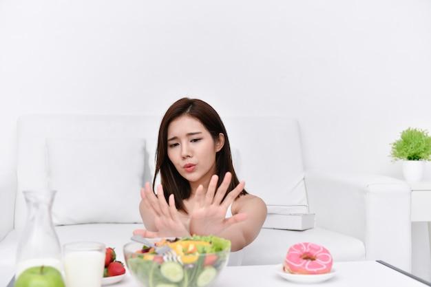 Gesundes essen-konzept schöne mädchen beschließen, mit ihren händen zu essen