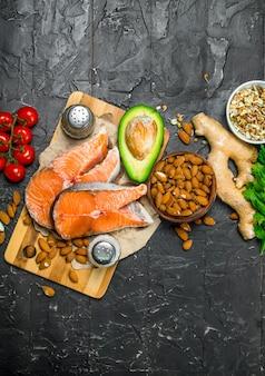 Gesundes essen. lachs mit gemüse und kräutern auf einem schwarzen rustikalen tisch.