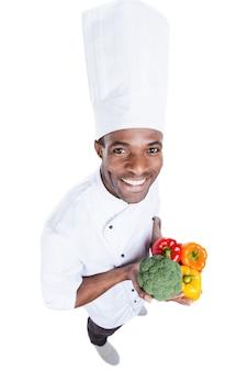 Gesundes essen liegt in seinen händen. blick von oben auf den fröhlichen jungen afrikanischen koch in weißer uniform