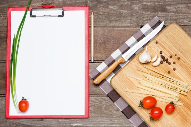 Gesundes essen, nudeln aus den harten weizensorten, tomaten, knoblauch auf holztisch. das notizbuch zum schreiben eines rezepts