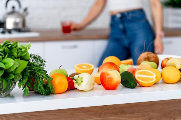 Gesundes essen, obst, gemüse, beeren, blattgemüse auf einem tisch im küchenhintergrund. bio-lebensmittel-konzept. moderne küche