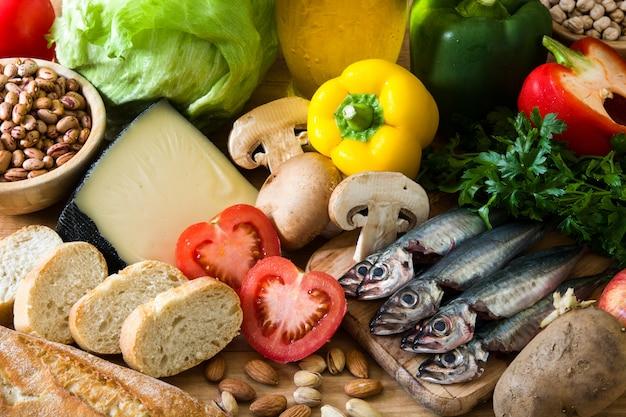 Gesundes essen. olivenöl und fische der mittelmeerdiät fruitvegetables-kornnüsse auf holztisch.