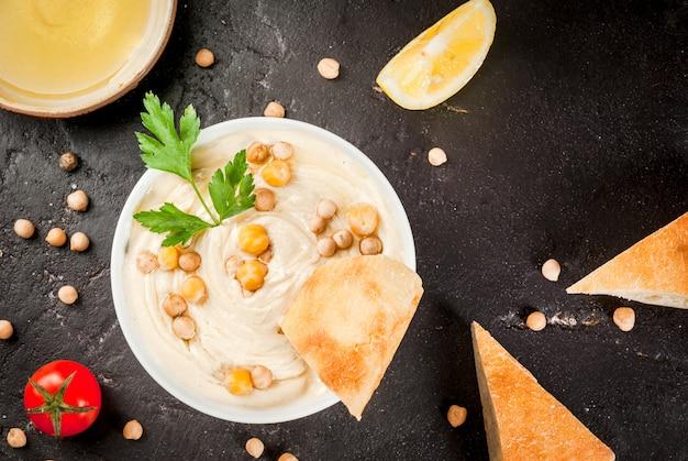 Gesundes essen. pflanzliche eiweißquellen. schüssel hummus auf schwarzer steintabelle mit den grüns gekocht und den rohen kichererbsen. mit frischen gurkentomaten karotten und fladenbrot.
