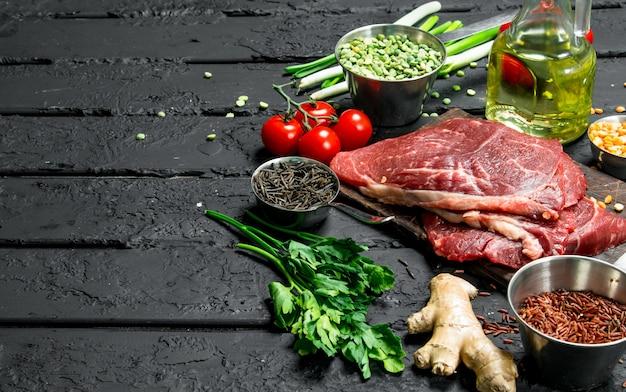 Gesundes essen. rohe rindersteaks mit bio-gemüse und gewürzen. auf einem schwarzen rustikalen hintergrund.