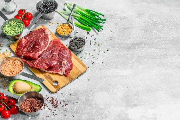 Gesundes essen. rohes rindfleisch mit bio-lebensmitteln. auf einem rustikalen hintergrund.