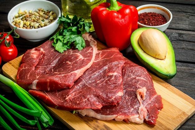 Gesundes essen. rohes rindfleisch mit bio-sortiment. auf einem holz.