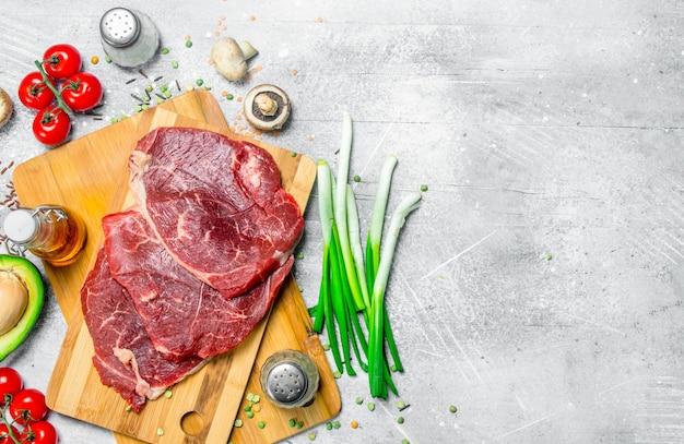 Gesundes essen. rohes rindfleisch mit einer vielzahl von bio-lebensmitteln. auf einem rustikalen hintergrund.
