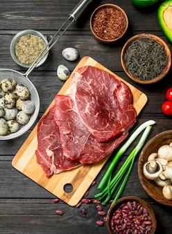 Gesundes essen. rohes rindfleisch mit einer vielzahl von bio-lebensmitteln und gewürzen. auf einem hölzernen hintergrund.