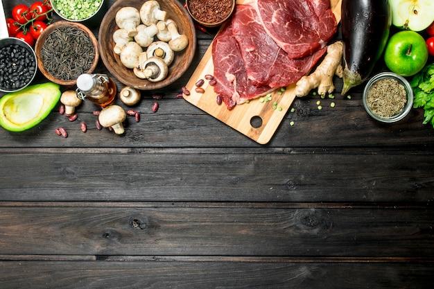 Gesundes essen. rohes rindfleisch mit einer vielzahl von bio-lebensmitteln und gewürzen auf holztisch.