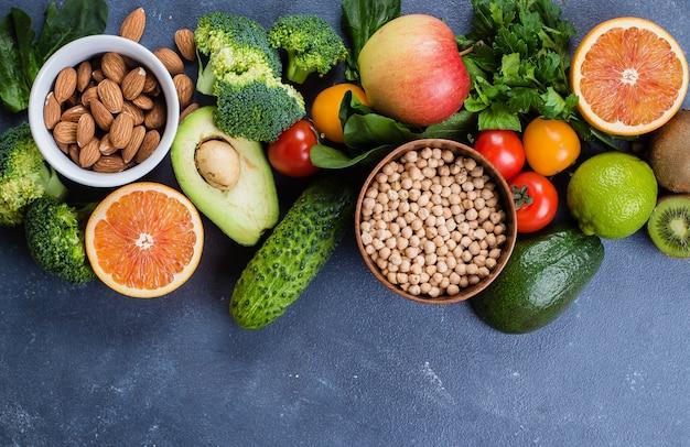 Gesundes essen sauber. rohe früchte, gemüse, nüsse, getreide auf konkretem steintabellenhintergrund