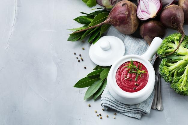 Gesundes essen, sauberes essenskonzept. saisonale herbst-herbst-gemüse cremige rote-bete-suppe mit zutaten auf einem küchentisch. draufsicht flach kopieren raumhintergrund