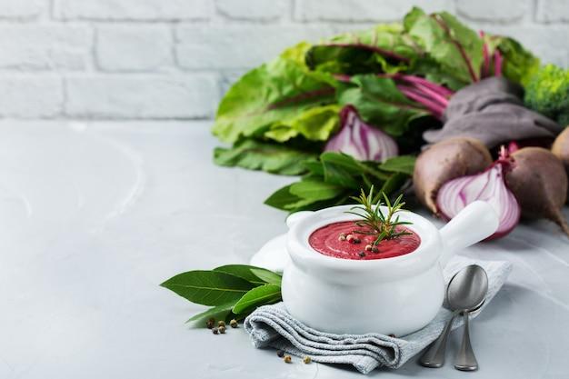 Gesundes essen, sauberes essenskonzept. saisonale herbst-herbst-gemüse cremige rote-bete-suppe mit zutaten auf einem küchentisch. raumhintergrund kopieren