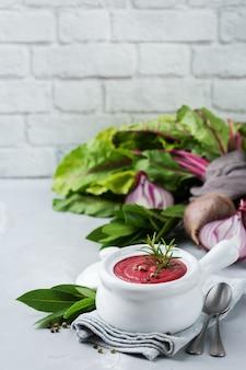 Gesundes essen, sauberes essenskonzept. saisonales herbst-herbstgemüse cremige rote-bete-suppe mit zutaten auf einem küchentisch