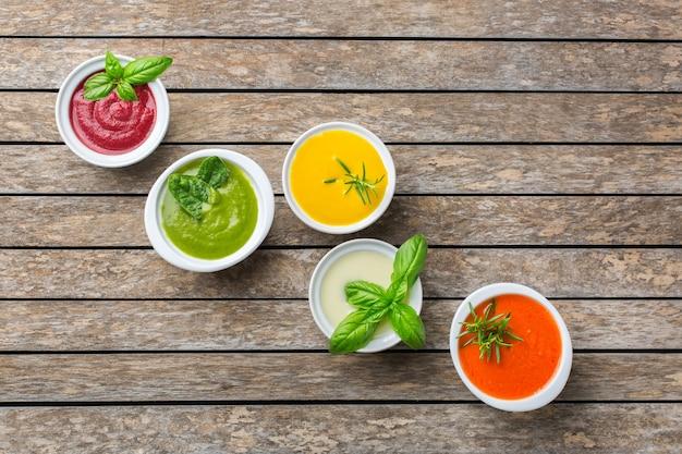 Gesundes essen, sauberes essenskonzept. vielzahl von bunten saisonalen herbstgemüse cremige suppen mit zutaten. kürbis, brokkoli, karotte, rote beete, kartoffel, tomatenspinat. flach legen, platz kopieren