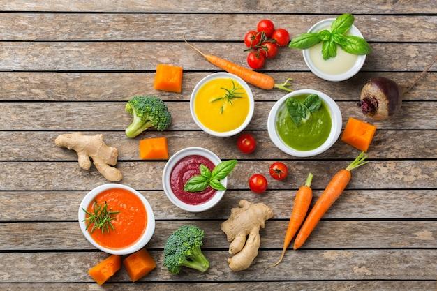 Gesundes essen, sauberes essenskonzept. vielzahl von bunten saisonalen herbstgemüse cremige suppen mit zutaten. kürbis, brokkoli, karotte, rote beete, kartoffel, tomatenspinat. flach legen