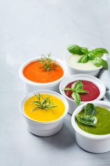 Gesundes essen, sauberes essenskonzept. vielzahl von bunten saisonalen herbstgemüse cremige suppen mit zutaten. kürbis, brokkoli, karotte, rote beete, kartoffel, tomatenspinat. platz kopieren