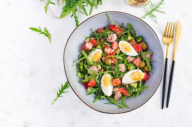Gesundes essen. thunfischsalat mit eiern, gurken, tomaten, oliven und rucola. französische küche. draufsicht, kopierraum, flache lage
