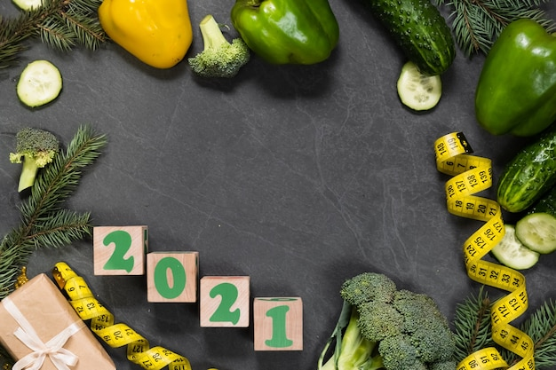 Gesundes essen und menü für weihnachten und neujahr tisch. draufsicht auf gemüse, maßband, gewichtsverlustkonzept an feiertagen. platz kopieren, einkaufsliste
