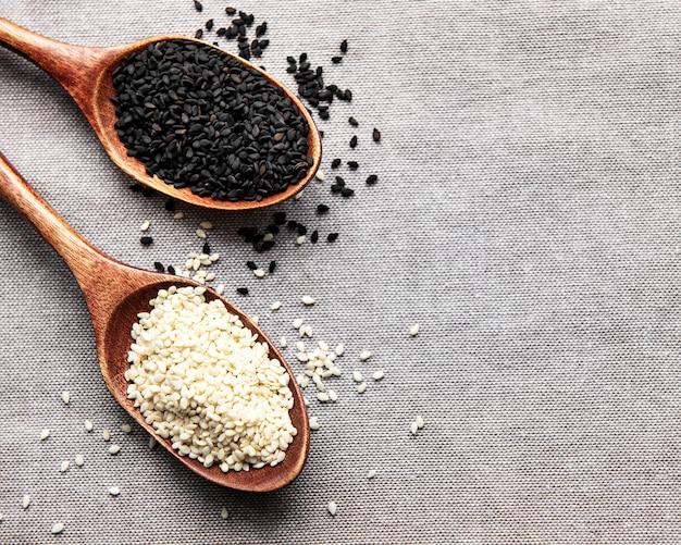 Gesundes essen und trinken konzept. schwarz-weiße sesamsamen in einem löffel auf textilem hintergrund