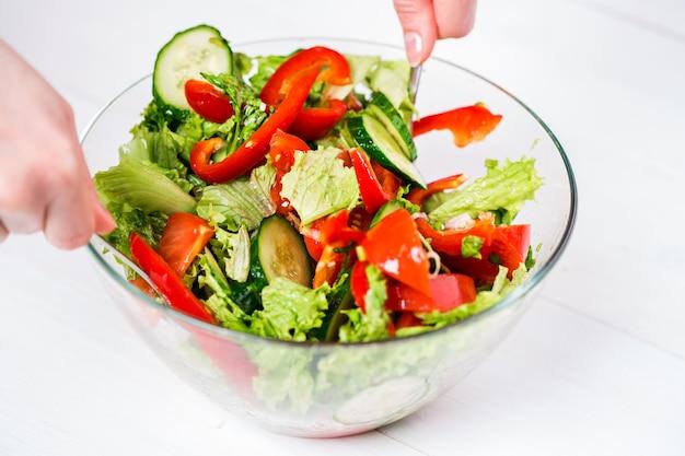 Gesundes essen, vegetarisches essen, diät und menschenkonzept - nahaufnahme einer jungen frau, die gemüsesalat mit olivenöl auf weißem hintergrund anzieht