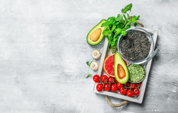 Gesundes essen. verschiedene bio-obst und gemüse mit schwarzem reis in holzkiste. auf einem rustikalen tisch.