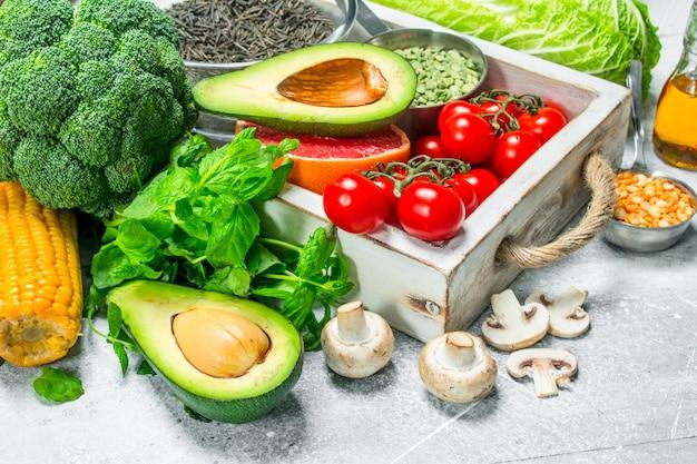 Gesundes essen. vielzahl von bio-gemüse und obst. auf einem rustikalen tisch.