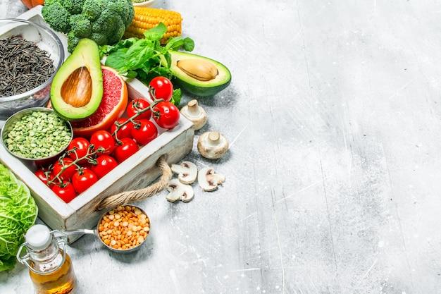 Gesundes essen. vielzahl von bio-gemüse und obst auf rustikalem tisch.