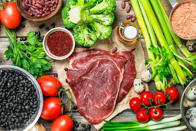 Gesundes essen. vielzahl von bio-lebensmitteln mit rohem rindfleisch. auf einem hölzernen hintergrund.