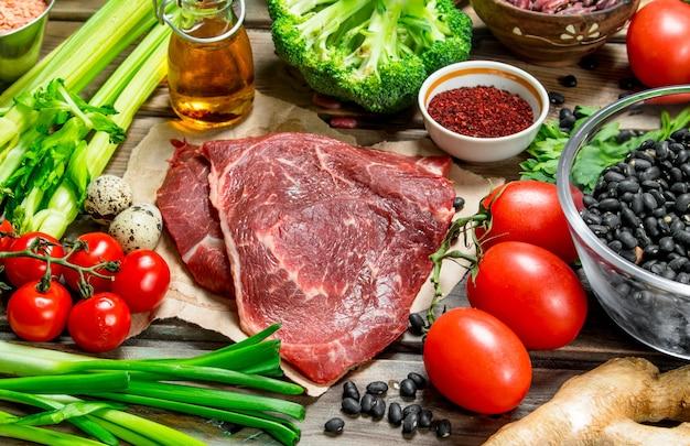 Gesundes essen. vielzahl von bio-lebensmitteln mit rohem rindfleisch. auf einem holztisch.