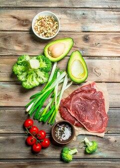 Gesundes essen. vielzahl von bio-lebensmitteln mit rohem rindfleisch auf holztisch.