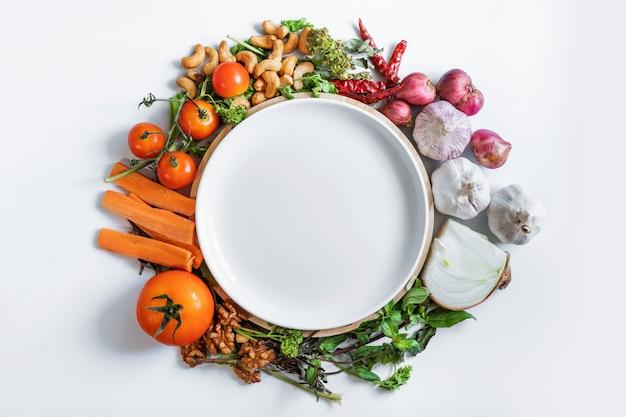 Gesundes essen. weiße keramikschale, die mit frischem bio-lebensmittelbestandteil, gemüse, kräutern und gewürzen, auf weißem hintergrund umgibt