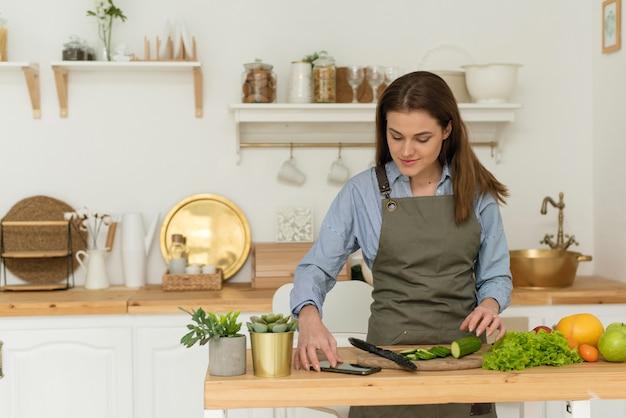 Gesundes essen zu hause. glückliche junge frau, die das telefon verwendet, das gemüsesalat in der küche zubereitet.