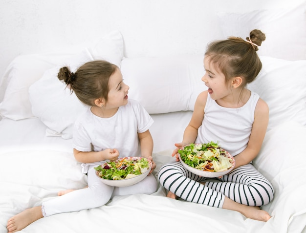 Gesundes essen zu hause. glückliche zwei süße kinder, die obst und gemüse im schlafzimmer auf dem bett essen. gesundes essen für kinder und jugendliche.