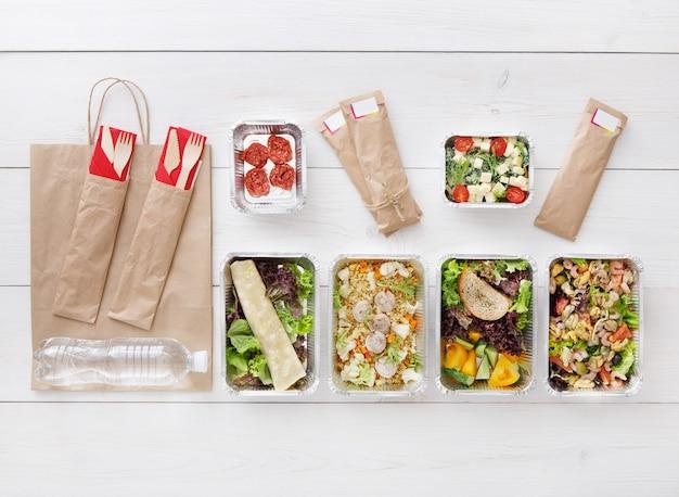 Gesundes essen zum mitnehmen in kisten draufsicht auf holz